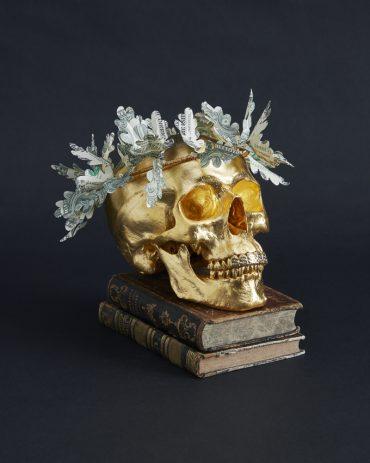 Gilded human skull sculpture with oak leaf wreath